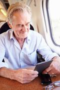 senior man reading e book on train journey - stock photo