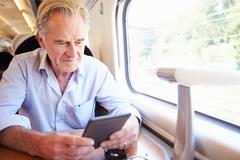 senior man reading e book on train journey - stock photo