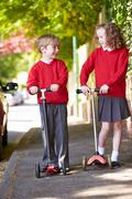 Boy and girl riding scooter on their way to school Stock Photos
