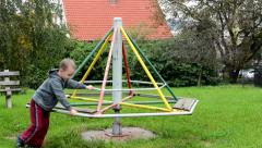 Child (a little boy) plays on the playground - roundabout Stock Footage