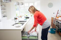 Woman standing in kitchen emptying waste bin Stock Photos