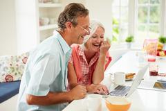 Middle aged couple looking at laptop over breakfast Stock Photos