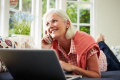 Middle aged woman ordering item on telephone Stock Photos