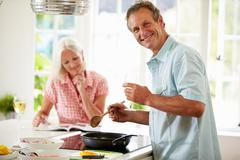 Middle aged couple cooking meal in kitchen together Stock Photos