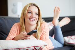 Teenage girl relaxing at home watching television Stock Photos