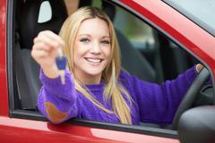 Teenage girl standing next to car holding key Stock Photos