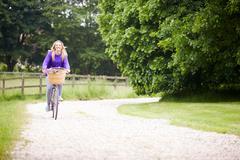 Teenage girl riding bike along country lane Stock Photos