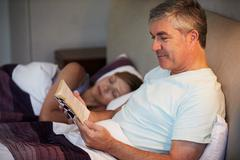 Middle aged couple in bed together with man reading book Stock Photos