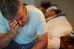 Man awake in bed suffering with insomnia Stock Photos