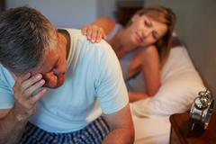 Wife comforting husband suffering with insomnia Stock Photos