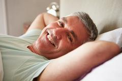 Middle aged man waking up in bed Stock Photos