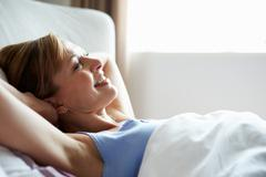 Attractive middle aged woman waking up in bed Stock Photos