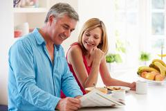 Middle aged couple having breakfast in kitchen together Stock Photos