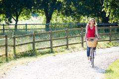 Attractive woman riding bike along country lane Stock Photos