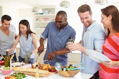 Group of friends having dinner party at home Stock Photos