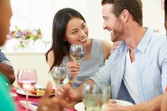 Group of friends sitting around table having dinner party Stock Photos