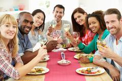 Group of friends sitting around table having dinner party Kuvituskuvat