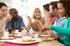 Group of friends having cheese and coffee dinner party Stock Photos