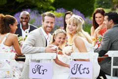 Bride and groom with bridesmaid at wedding reception Stock Photos