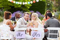 Bride and groom enjoying meal at wedding reception Stock Photos