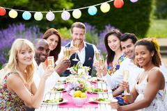 Group of friends enjoying outdoor dinner party Stock Photos
