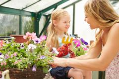 Mother and daughter growing plants in greenhouse Stock Photos