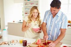Couple preparing healthy breakfast in kitchen Stock Photos