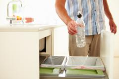 Close up of man recycling kitchen waste in bin Stock Photos