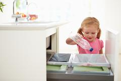 Girl recycling kitchen waste in bin Stock Photos