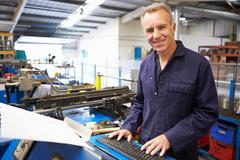 Factory engineer operating hydraulic tube bender Stock Photos