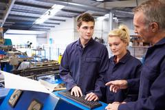 Engineer teaching apprentices to use tube bending machine Stock Photos