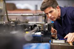 Factory engineer operating hydraulic tube bender Stock Photos