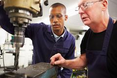 Engineer teaching apprentice to use milling machine Stock Photos