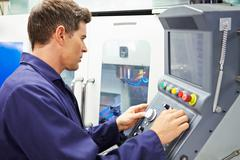 Engineer operating computer controlled milling machine Stock Photos