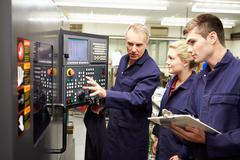 engineer teaching apprentices to use computerized lathe - stock photo