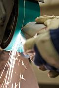 Close up of engineer using grinding machine in factory Stock Photos
