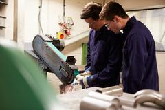 Engineer teaching apprentice to use grinding machine Stock Photos