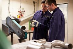 Engineer teaching apprentice to use grinding machine Stock Photos