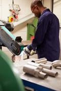 Engineer using grinding machine in factory Stock Photos