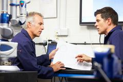 Two engineers discussing plans with cmm arm in foreground Stock Photos