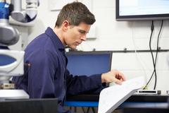 Engineer looking at plans with cmm arm in foreground Stock Photos