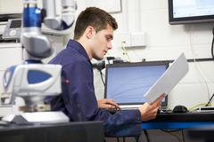 Trainee engineer studying plans with cmm arm in foreground Stock Photos