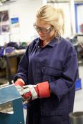 Apprentice engineer working on factory floor Stock Photos