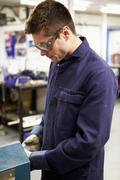 apprentice engineer working on factory floor - stock photo