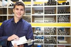 Apprentice checking stock levels in store room Stock Photos