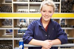 Portrait of female engineering apprentice in store room Stock Photos