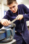 Apprentice engineer working on factory floor Stock Photos