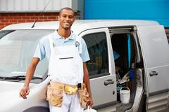decorator wearing overalls standing next to van - stock photo