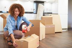 Woman sealing boxes ready for house move Stock Photos