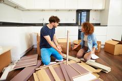 Couple putting together self assembly furniture in new home Stock Photos